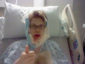 Me, bloodied in bandages in a hospital bed, giving a thumbs up, immediately after jaw surgery.